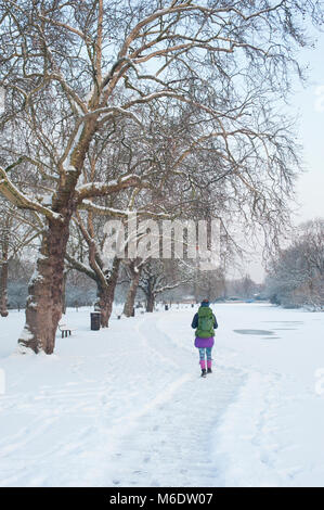 A woman walking along a snow covered path in Regents Park during winter,(early morning, February 2018), London, - Stock Image