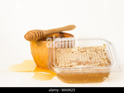 Cut honeycomb in a plastic container, honey in a wooden bowl and a wooden honey dipper. - Stock Image