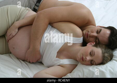 Pregnant wife and husband sleeping together - Stock Image