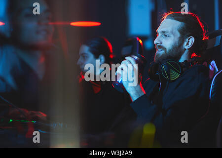 Smiling satisfied young bearded gamer with headphones on neck sitting in comfortable armchair and drinking energy beverage while playing video game - Stock Image