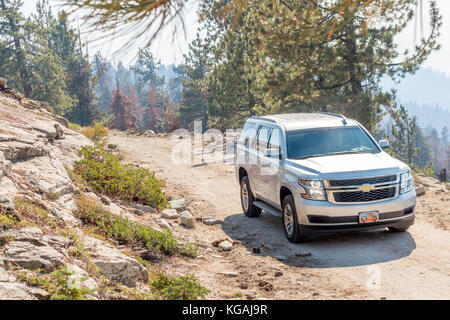Big SUV Chevrolet Tahoe Full size SUV Brand new 2018 Chevy Tahoe LT on dirt road in the mountains of Sequoia National - Stock Image