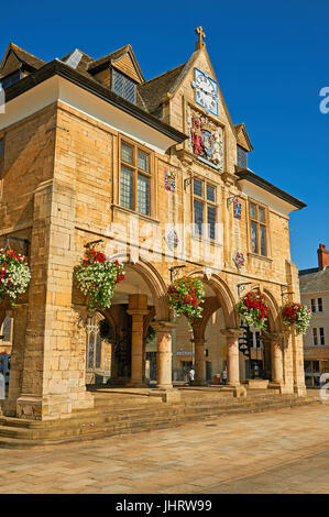 The old market hall in the centre of Peterborough seen in the summer bedecked in hanging baskets - Stock Image
