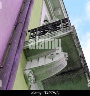 Details of old medieval style building from below. The building has green and purple concrete walls and beautiful balconies. Photographed in Nyon. - Stock Image