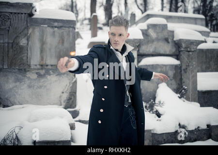Young man in image of black magician makes a spell using magic wand next to crypt. - Stock Image