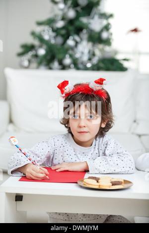 Boy Wearing Headband Writing Letter To Santa Claus - Stock Image