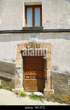 Door with stone lintel with coat of arms of a XIX century building that housed the town hall and the school in Gistaín (Chistau, Huesca, Aragon,Spain) - Stock Image