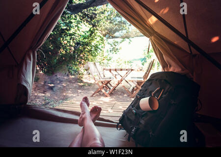 view of crossed feet of a hiker person resting barefoot in a camping tent, travel discovery concept, point of view shot - Stock Image
