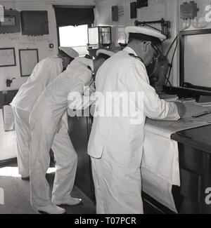 1950s, steamship officers working on charts on the ship. - Stock Image