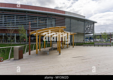 Covered seating area on a wooden boardwalk with some modern architecture in the background; Rushden Lakes, Northamptonshire, UK - Stock Image