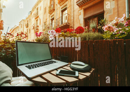 Cozy beautiful workspace on balcony with laptop, smartphone, wooden fence and a lot of flowers, sunny summer day, - Stock Image