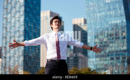 Businessman relaxing outdoors during daytime - Stock Image