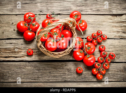 Ripe tomatoes in a basket. On a wooden background. - Stock Image