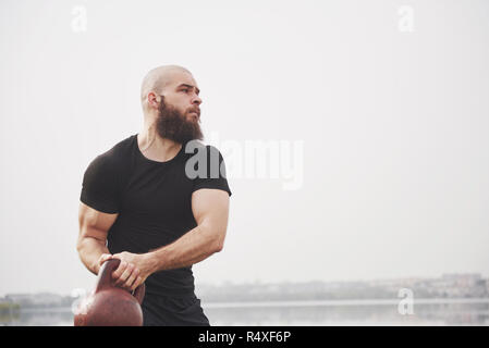 The bearded young man is engaged in outdoor sports - Stock Image