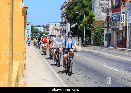 Cyclists on a tour, cycling on the road in Vedado, Havana, Cuba - Stock Image
