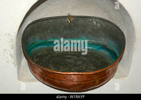 nostalgic and antique stoup with clear holy water, holy water in an old stoup made of copper with verdigris in the inside attached to a wall alcove in - Stock Image