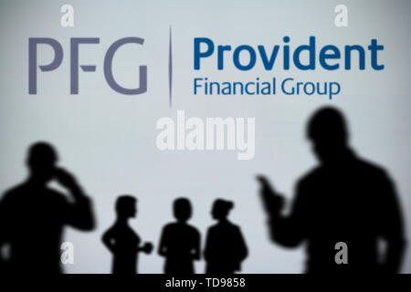 The Provident Financial Group (PFG) logo is seen on an LED screen in the background while a silhouetted person uses a smartphone (Editorial use only) - Stock Image