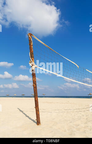 Torn volleyball net on the beach with cloudy blue sky and yellow sand in the morning - Stock Image