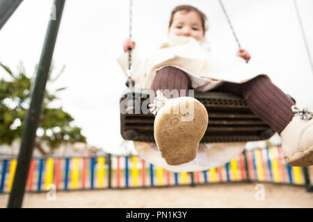 Happy baby girl having fun on a swing on winter. Dirty children shoes concept - Stock Image