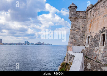 Part of the Morro Castle with the skyline of Havana Cuba across the harbour. - Stock Image