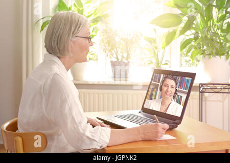 Senior woman in her sunny living room in front of a laptop making notes during watching an online advice video by - Stock Image