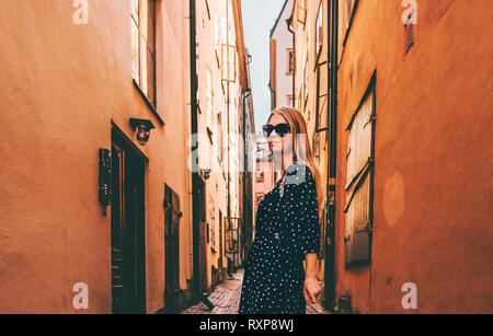 Blonde woman walking in Stockholm  traveling alone fashion lifestyle summer vacations in Sweden old city street - Stock Image