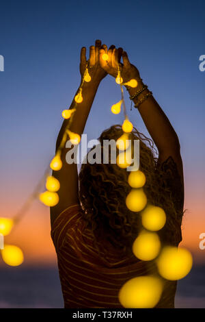 Romantic woman viewed from back with lot of yellow lights - emotion and wanderlust concept for people enojying romance and outdoor leisure - night sho - Stock Image