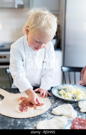 Boy making pizza in kitchen - Stock Image