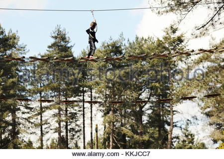boy high on high wire bridge - Stock Image