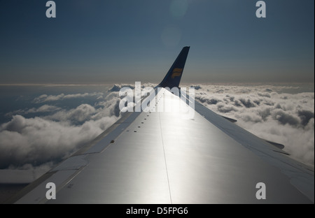 View looking down on clouds from aeroplane window over wing - Stock Image