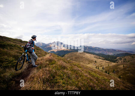 Male backpacker leaning on bicycle on grassy mountain against sky - Stock Image