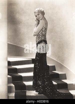 Woman in sequined gown standing on staircase - Stock Image