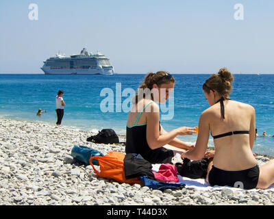 Nice Cote dAzur France - Two girls sitting on the Promenade des Anglais beach with a cruise ship passing - Stock Image