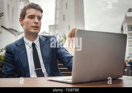 Young attractive businessman sitting at street cafe next to laptop and looking at monitor. - Stock Image
