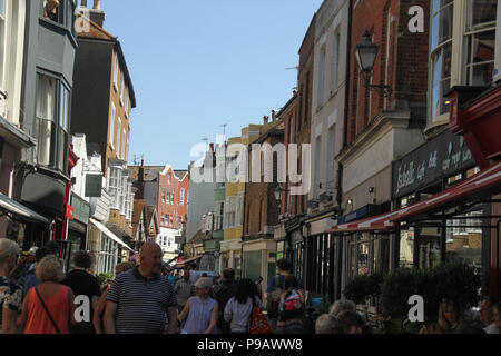 Hastings, UK -July 14 2018: People seen walking on George Street in Hastings Old Town on a hot summers day as the temperatures sore to above 27 degrees on 14 July 2018. Hastings on the south coast of England is 53 miles south-east of London and is 8 miles from where the  Battle of Hastings took place in October 1066. Credit: David Mbiyu /Alamy Live News - Stock Image