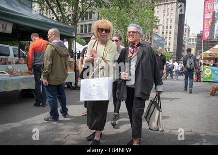 Two youthfull looking middle age women walk through the Union Square Green Market chatting and holding shopping bags. In New York City. - Stock Image