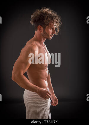 Naked muscular man covering crotch with towel - Stock Image