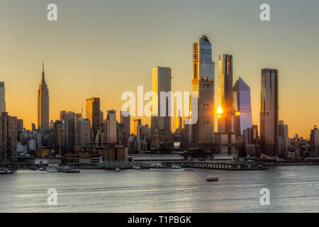 Sunrise reflected off the mixed-use Hudson Yards development and other buildings on the West Side of Manhattan in New York City at sunrise. - Stock Image