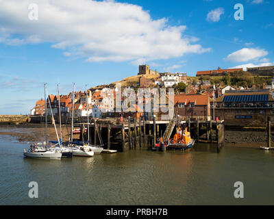 Whitby harbour with the RNLI lifeboat station and St Mary's church in autumn afternoon sunlight - Stock Image