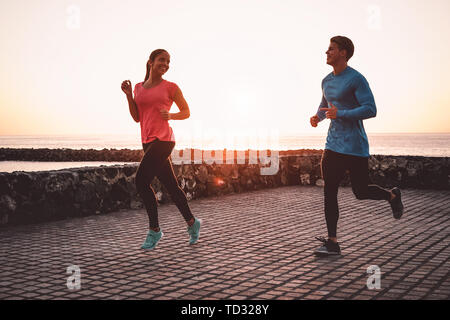 Fit couple jogging next the beach - Sporty young people doing run workout session outdoor - Healthy, youth and sport activity lifestyle concept - Stock Image
