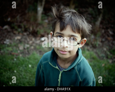 Boy looking over top of glasses - Stock Image