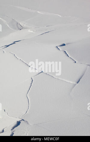 Cracks are appearing in the snow-covered ice on a lake - Stock Image