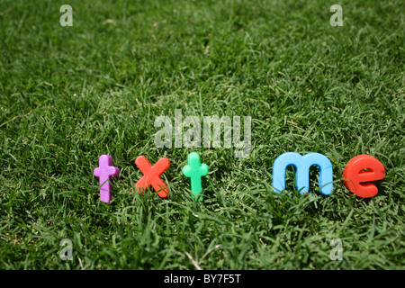 The words 'txt me' spelled out in colourful plastic letters, on green grass, taken from a low angle - Stock Image