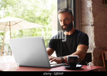 Handsome Bearded Businessman Wearing Black Tshirt Working Laptop Wood Table Urban Cafe.Young Manager Work Notebook - Stock Image