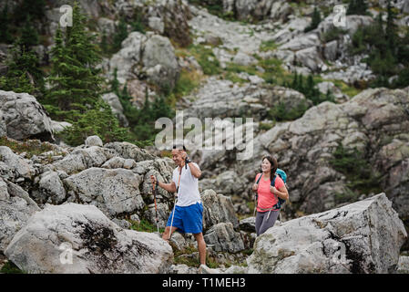 Couple hiking through rugged landscape - Stock Image
