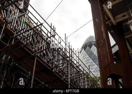 London Gherkin Building in the background with scaffolding and construction works on new buildings in the foreground - Stock Image