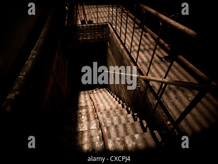 Inhospitable basement entrance staircase of decaying abandoned power station - Stock Image