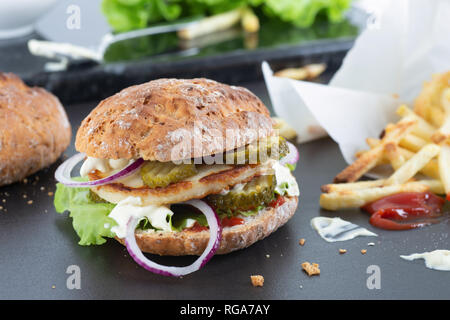Gluten free, vegetarian halloumi burger with ketchup, red onion, pickled cucumber, lettuce and creme fraiche with some mustard. - Stock Image