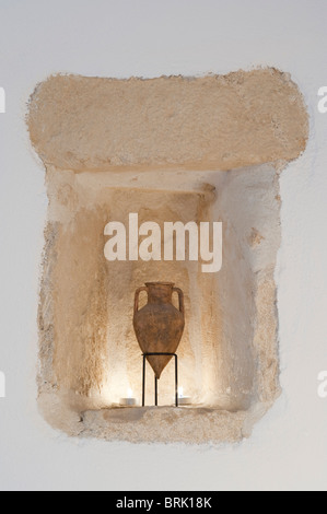 Limestone alcove with Greek urn miniature illuminated by candles - Stock Image