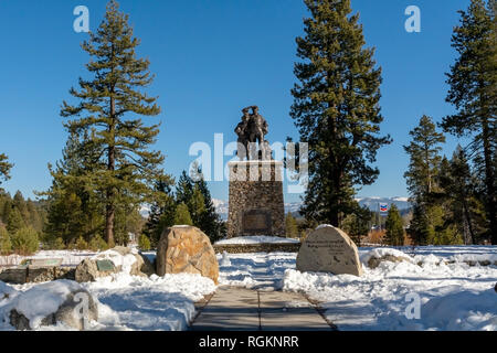 Truckee, CA , USA - January 14, 2019: Monument at Donner Memorial State Park Visitors center on a winters day with accumulated snow and blue sky - Stock Image