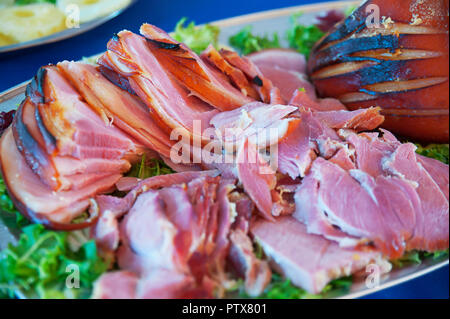 Tasty pork meat slices with crunchy skin cooked on the grill, set on a bed of lettuce, at a buffet bar, or self-service restaurant - Stock Image